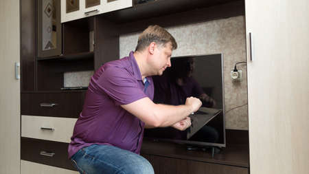 A satisfied blonde man removes a protective film from a newly purchased LCD TV. 版權商用圖片