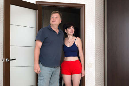 An adult married couple of tourists are happy to look at their hotel room.
