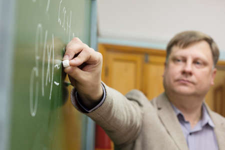 Professor of the Department of Applied Mathematics in classroom at the blackboard writes formulas for students.