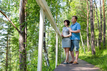 A man and a woman on vacation in a green forest are standing on the bridge embracing and looking. 版權商用圖片