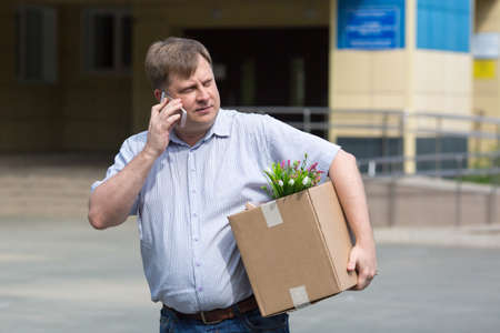 A fired manager with a box of personal belongings on the street calls an ad in search of a new job.