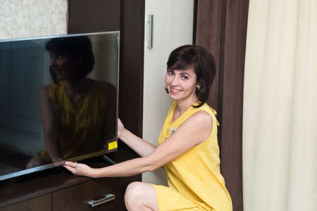 A brunette woman in the apartment installs a new large LCD TV on the table.