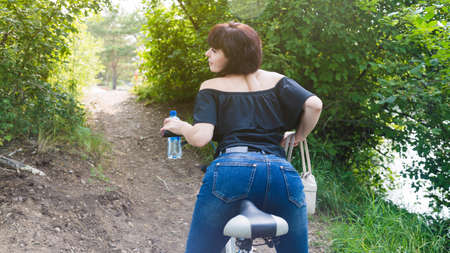 A brunette woman on bicycle arches her back like a cat, a beautiful athletic figure.