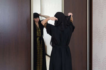 A Muslim woman dresses up front of a mirror and puts on a burqa in her apartment.