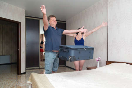 A married couple happily checks into a hotel and throws a suitcase on the bed. 版權商用圖片