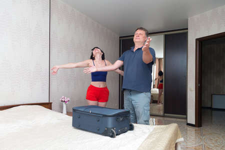 A married couple happily checks into a hotel and throws a suitcase on bed.