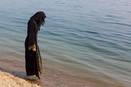 A Muslim woman national clothes wets her feet in the sea. 版權商用圖片