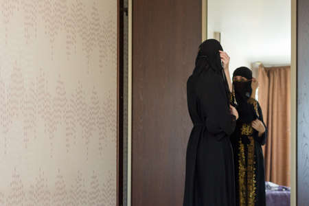 A Muslim woman dresses up in front of mirror and puts on a burqa in her apartment. 版權商用圖片
