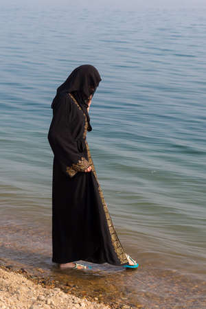 A Muslim woman in national clothes wets her feet the sea.