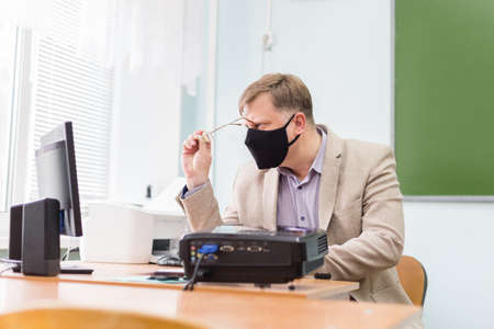 A teacher at school at his desk in a protective black mask is trying to see through his glasses the recording on the computer.