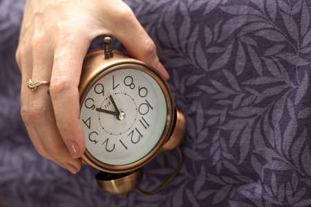 A woman's hand with an alarm clock hanging from the bed. The concept of a difficult awakening, an early rise. 版權商用圖片