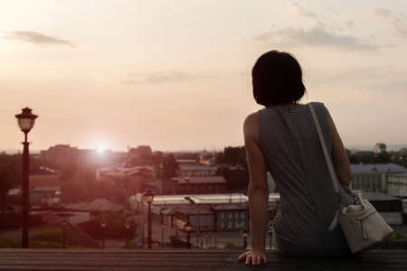 A lonely woman looks at the city at sunset from the observation deck rear view. 版權商用圖片
