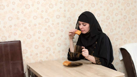 A Muslim woman in national clothes having breakfast at the table in her apartment.