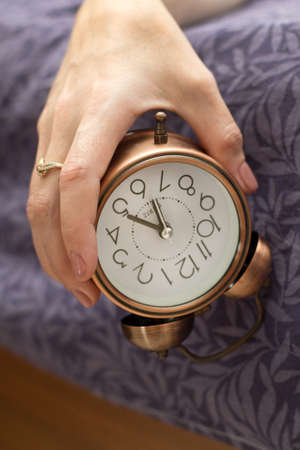 A woman's hand with an alarm clock hanging from the bed The concept of a difficult awakening an early rise.