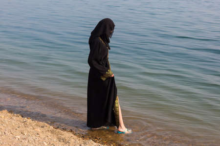 A Muslim woman in national clothes wets her feet in sea.