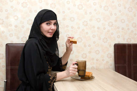 A Muslim woman in national clothes is having breakfast at the table in her apartment. 版權商用圖片