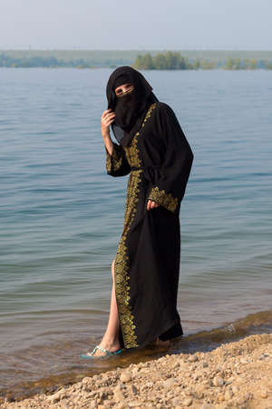 A Muslim woman in national clothes wets her feet in the sea.,