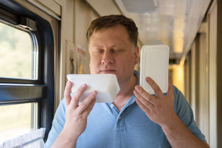 A man on the train with instant noodles in his hands closed his eyes and enjoys the smell.