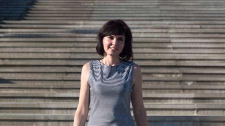 Woman brunette striped dress descends a wide staircase. 版權商用圖片
