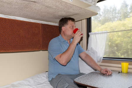 A man in a compartment car drinks tea with pleasure from a red mug and looks out the window.