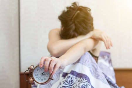 A sleepy woman is sitting on bed with her face buried in her knees and holding an alarm clock in her hands. concept of not falling asleep, heavy awakening. 版權商用圖片