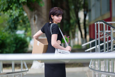 A happy brunette in a black dress with a box of personal belongings is in a hurry for a new job, an employment concept.