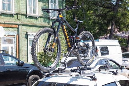 Irkutsk, Russia - July 25, 2021, Sports mountain bike carried in the roof rack of a car