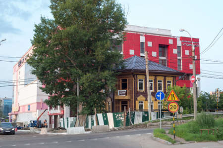 Irkutsk, Russia - July 25, 2021, Historic old building in disrepair against the background of a modern shopping center