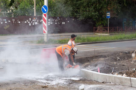 Irkutsk, Russia - July 25, 2021, Two workers install a road curb