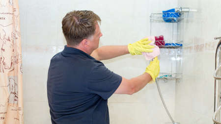 A man is cleaning the bathroom wiping shower hose.