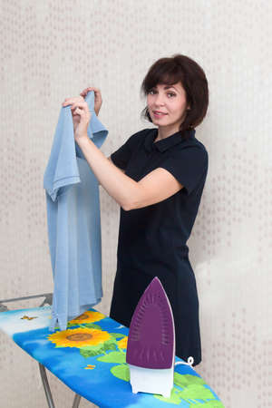 A brunette woman in her apartment with smile irons men clothes.