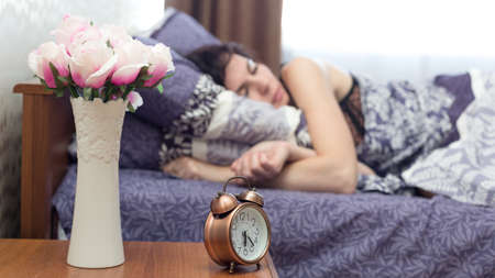 sound of a loud alarm clock can not wake up a woman who is fast asleep.