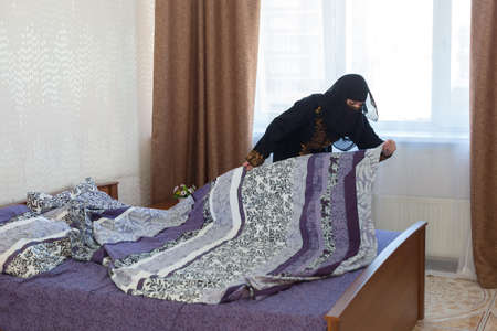 A Muslim woman makes her bed in her apartment, the concept of household chores. 版權商用圖片