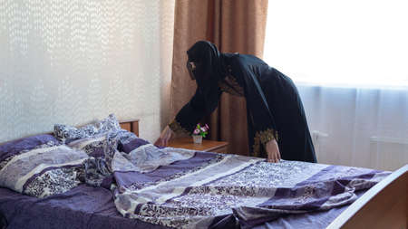 Muslim woman makes her bed in her apartment the concept of household chores.