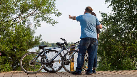 man and a woman riding bicycles stopped by river to enjoy nature.