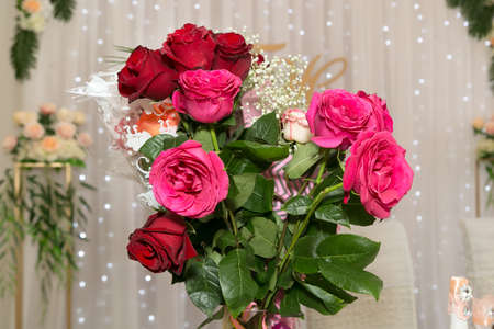 A beautiful large bouquet of scarlet roses in a vase on the festive table.
