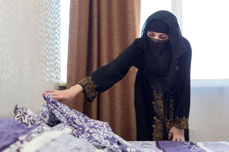 A Muslim woman makes her bed in her apartment  concept of household chores.