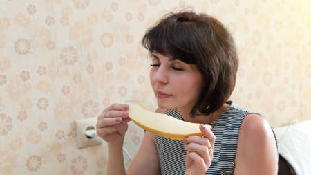woman with a fragrant melon in her hands closed her eyes with pleasure