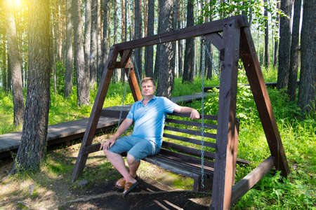 Portrait of an adult man resting in the park on wooden swing on summer day. 版權商用圖片