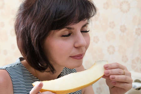 A woman with a fragrant melon in her hands closed her eyes with pleasure. 版權商用圖片