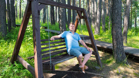 Portrait of an adult man resting in park on a wooden swing on a summer day.
