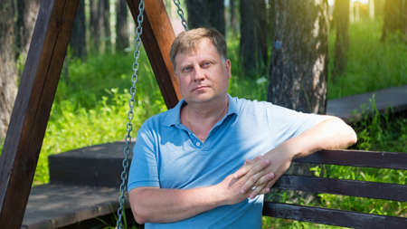 Portrait of adult man resting in the park on a wooden swing on a summer day.