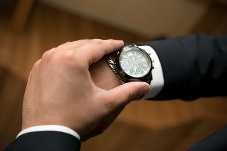 A man looks at his wristwatch afraid of being late for a date.