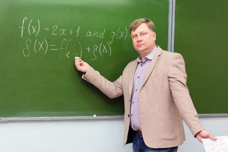 A strict math teacher at the blackboard explains the solution of the problem to students. 版權商用圖片