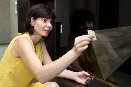 A woman in a yellow dress with a smile on her face removes a protective film from a new LCD TV.