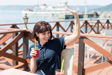 brunette in a cafe by the sea with a glass of juice happily waves to the waiter.