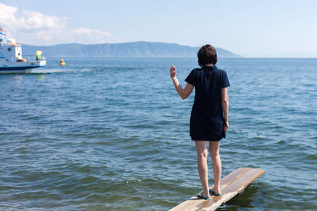 A woman with sadness on the pier sees off her beloved sailing away on a ship waving her hand after him. 版權商用圖片