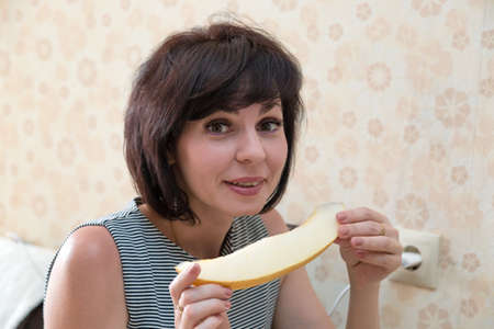 A woman with fragrant melon her hands closed her eyes with pleasure.