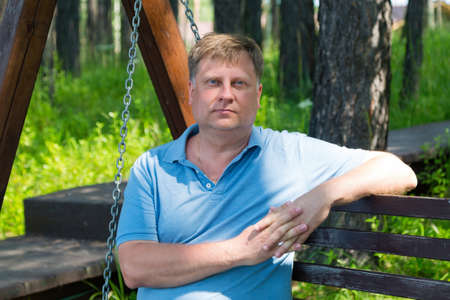 Portrait of an adult man resting in the park on a wooden swing on a summer day. 版權商用圖片