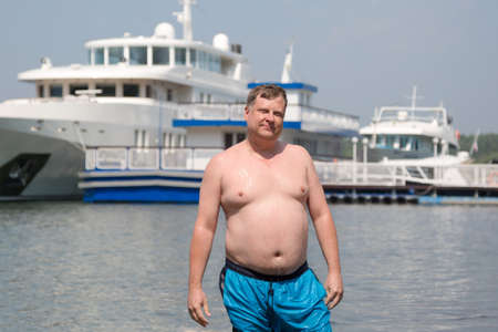 A young oligarch swims in the sea against the background of his own yacht.